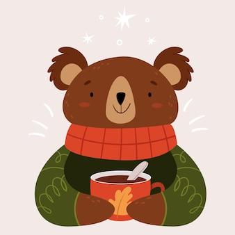 Un ours très mignon avec une écharpe rouge chaude et une grande tasse de cacao.