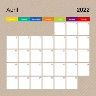 Page de calendrier pour avril 2022, planificateur mural au design coloré. la semaine commence le lundi.