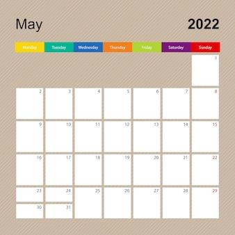 Page de calendrier pour mai 2022, planificateur mural au design coloré. la semaine commence le lundi.