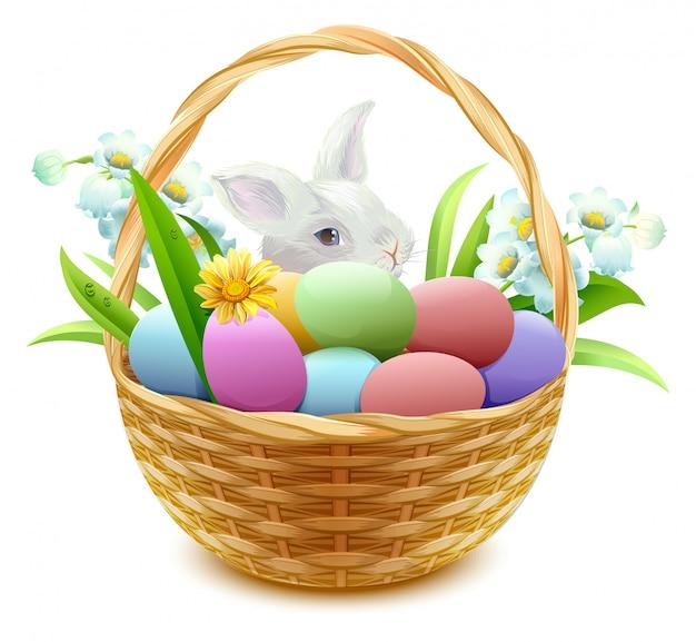 Panier en osier avec oeufs de pâques, fleurs et lapin