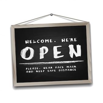 Panneau ouvert sur tableau noir dans un cadre en bois. panneau d'information pour devant la porte sur le travail à nouveau. gardez une distance sociale et portez un masque facial. isolé sur blanc.