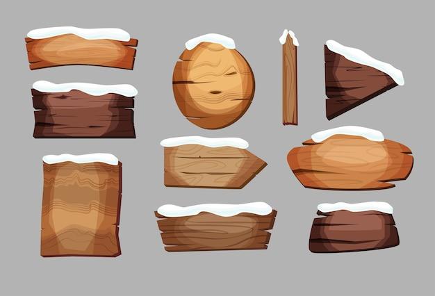 Panneaux vides ou planches de bois de différentes couleurs et textures avec de la neige dessus.