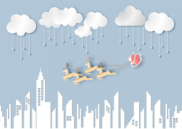 Papier d'art du père noël avec rennes sur fond de ciel et ville bleu