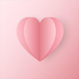 Papier découpé en forme de coeur rose placé sur fond dégradé rose