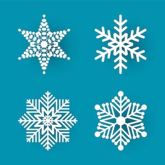 Papier de noël coupé de quatre flocons de neige blancs