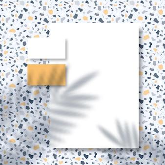 Papier à en-tête et cartes de visite sur une surface de motif terrazzo avec une superposition d'ombre de feuilles de palmier tropical
