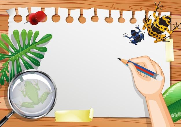 Papier vierge sur la vue de dessus de table avec des feuilles et des éléments de grenouille