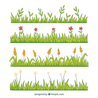 Paquet de quatre frontières d'herbe dessinés à la main avec des fleurs