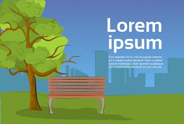 Parc public en soirée avec un banc en bois sous un arbre et une vue sur la ville. modèle de texte