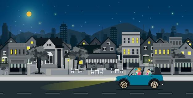 Parents et enfants conduisant dans les rues de la ville la nuit