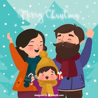 Des parents heureux et leur enfant sous la neige