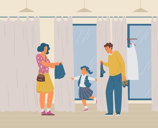 Parents avec leur fille essayant un nouveau formulaire scolaire dans la cabine d'essayage