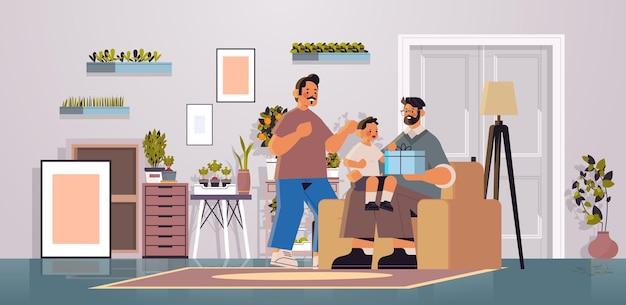 Les parents masculins présentent une boîte-cadeau au petit-fils de la famille gay transgenre amour concept de communauté lgbt