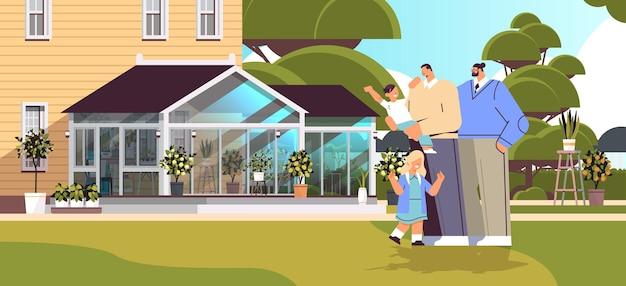 Les parents de sexe masculin debout avec de petits enfants sur la pelouse de l'arrière-cour famille gay transgenres aiment le concept de communauté lgbt