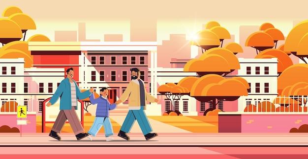 Parents de sexe masculin marchant avec petit fils famille gay transgenre amour communauté lgbt concept coucher de soleil paysage urbain fond illustration vectorielle horizontale pleine longueur