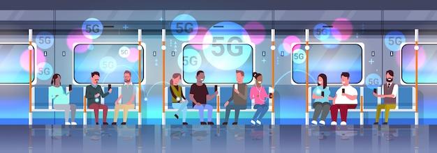 Les passagers du métro à l'aide de téléphones intelligents en ligne sans fil connexion au système de transport public de la ville du métro souterrain intérieur horizontal pleine longueur