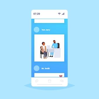 Patient recevant une prescription homme afro-américain en consultation avec un médecin de sexe masculin assis sur le lieu de travail médecine et soins de santé concept smartphone écran application mobile pleine longueur