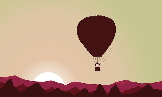 Paysage de colline avec des silhouettes de montgolfière