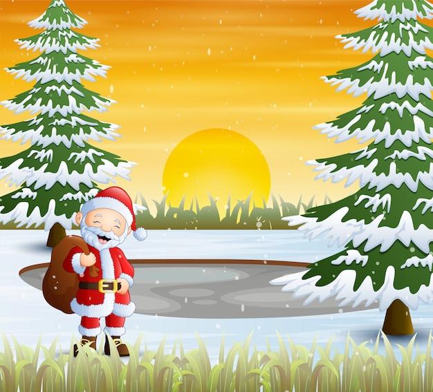 Paysage d'hiver avec le père noël tenant un sac de cadeaux