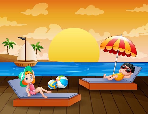 Paysage de mer avec garçon et fille se détendre sur une chaise longue