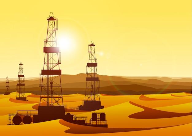 Paysage avec des plates-formes pétrolières dans le désert aride avec des dunes de sable.