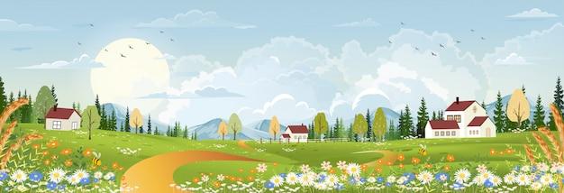 Paysage de printemps avec une nature rurale paisible au printemps avec des terres d'herbe sauvage, maison de ferme, montagne, soleil, ciel bleu et nuages