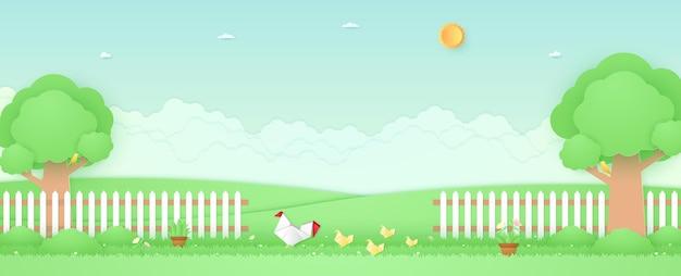 Paysage de printemps poulet et poussin en origami dans le jardin avec des fleurs d'arbres sur l'herbe et la clôture