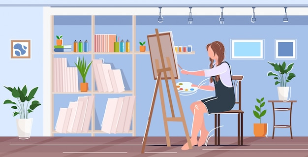 Peintre à l'aide de pinceau et palette femme artiste assis en face de chevalet art concept atelier moderne studio intérieur horizontal
