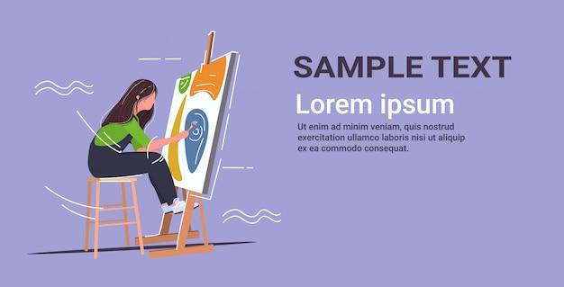 Peintre à l'aide de pinceau et palette femme artiste assis en face de chevalet art concept copie espace horizontal