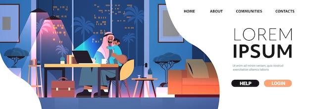 Père arabe occupé indépendant avec petit fils regardant dans un écran d'ordinateur portable concept de paternité indépendant nuit sombre salon intérieur pleine longueur horizontale copie espace