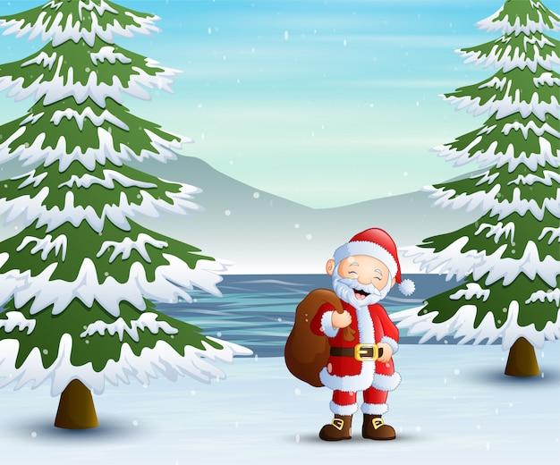 Père noël debout avec sac de cadeaux en forêt