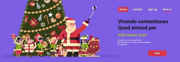 Père noël avec elfes de race de mélange prenant selfie avec bannière de cadeaux