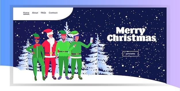 Père noël avec mix race elfes prenant selfie photo sur smartphone appareil photo vacances de noël célébration concept nuit forêt chute de neige page de destination