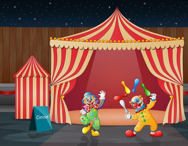Performance de clowns heureux dans le chapiteau de cirque