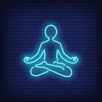 Personne assise en posture de lotus et méditant sur une enseigne au néon