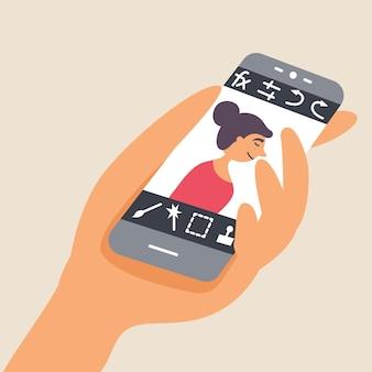 Une personne traite une photo sur un smartphone via un éditeur mobile