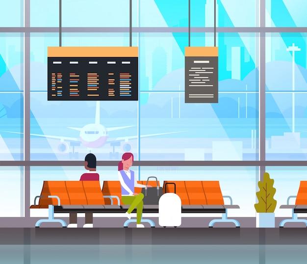 Personnes en attente de décollage dans le hall de l'aéroport