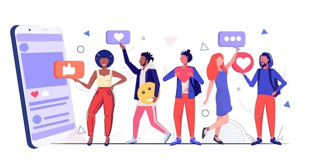 Personnes détenant des icônes de médias sociaux réseau chat bulle communication concept mix race hommes femmes à l'aide de l'application mobile en ligne croquis horizontal pleine longueur