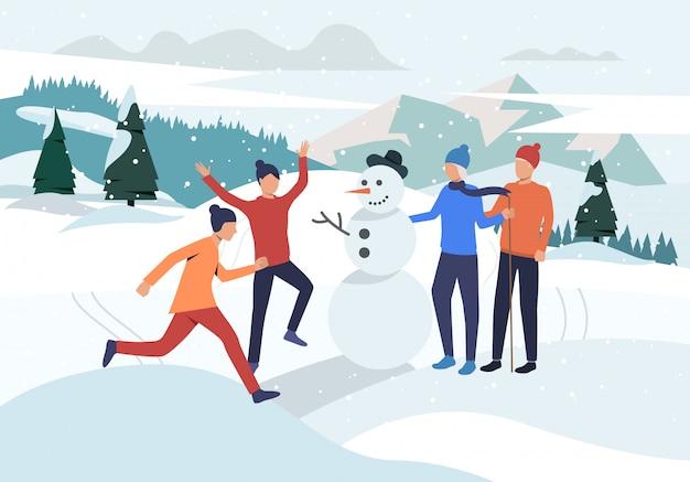 Personnes faisant la page d'atterrissage de bonhomme de neige