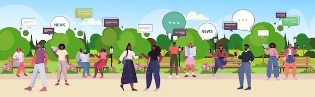 Personnes lisant les journaux et discutant du concept de communication de bulle de discussion de nouvelles quotidiennes. mix race hommes femmes marchant dans le parc urbain illustration horizontale pleine longueur