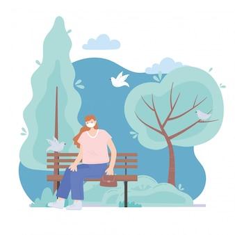 Personnes avec masque médical, jeune femme assise sur un banc dans le parc
