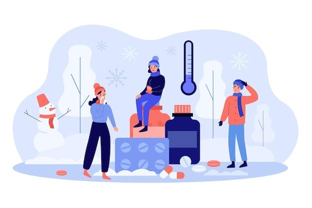 Les personnes se sentant mal à cause de la température basse à l'extérieur, souffrant d'allergie au froid. personnages en vêtements chauds debout près de pilules à l'extérieur