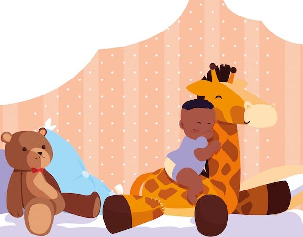 Petit garçon afro dormant avec une girafe en peluche et un ours en peluche