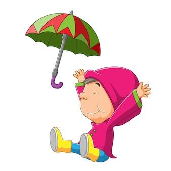 Le petit garçon est assis et jette le parapluie coloré de l'illustration