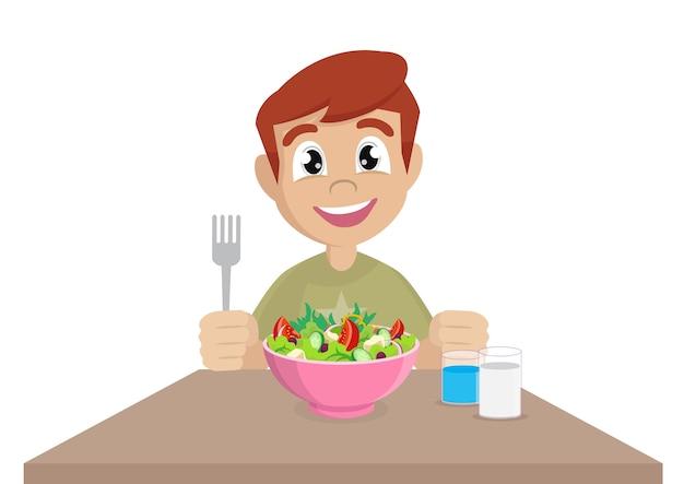 Un petit garçon heureux de manger de la salade
