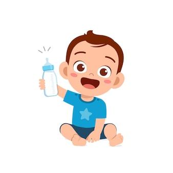 Le petit garçon mignon boit du lait de la bouteille