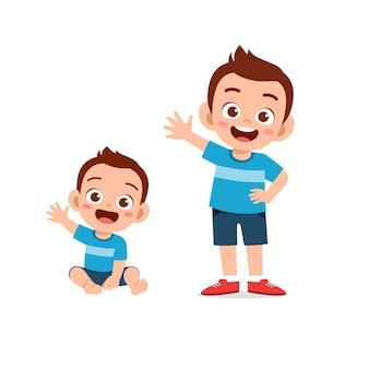 Le petit garçon mignon dit bonjour avec le jeune frère