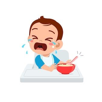 Le petit garçon mignon rejette la nourriture saine