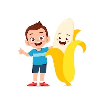 Le petit garçon mignon se tient avec le caractère de banane