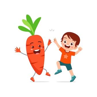Le petit garçon mignon se tient avec le caractère de carotte